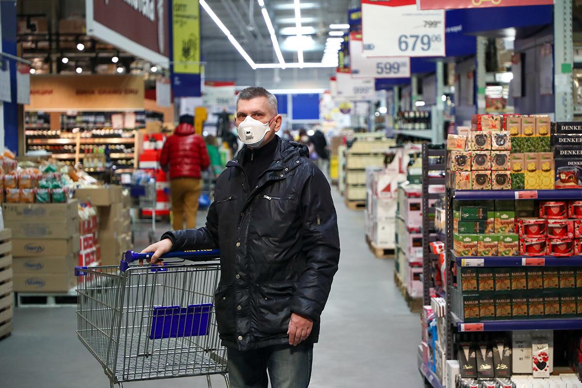 Покупатель у витрины с продовольственными товарами в супермаркете METRO. Ранее многие торговые центры ввели новые меры для ограничения концентрации посетителей из-за угрозы распространения коронавируса COVID-19