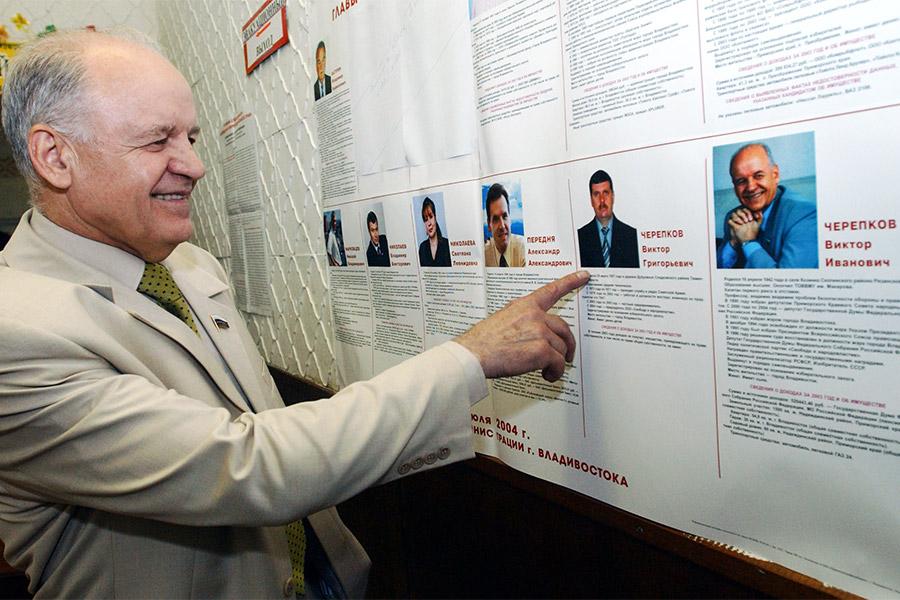 Виктор Черепков на избирательном участке Владивостока у фотографии своего однофамильца. 2004 год