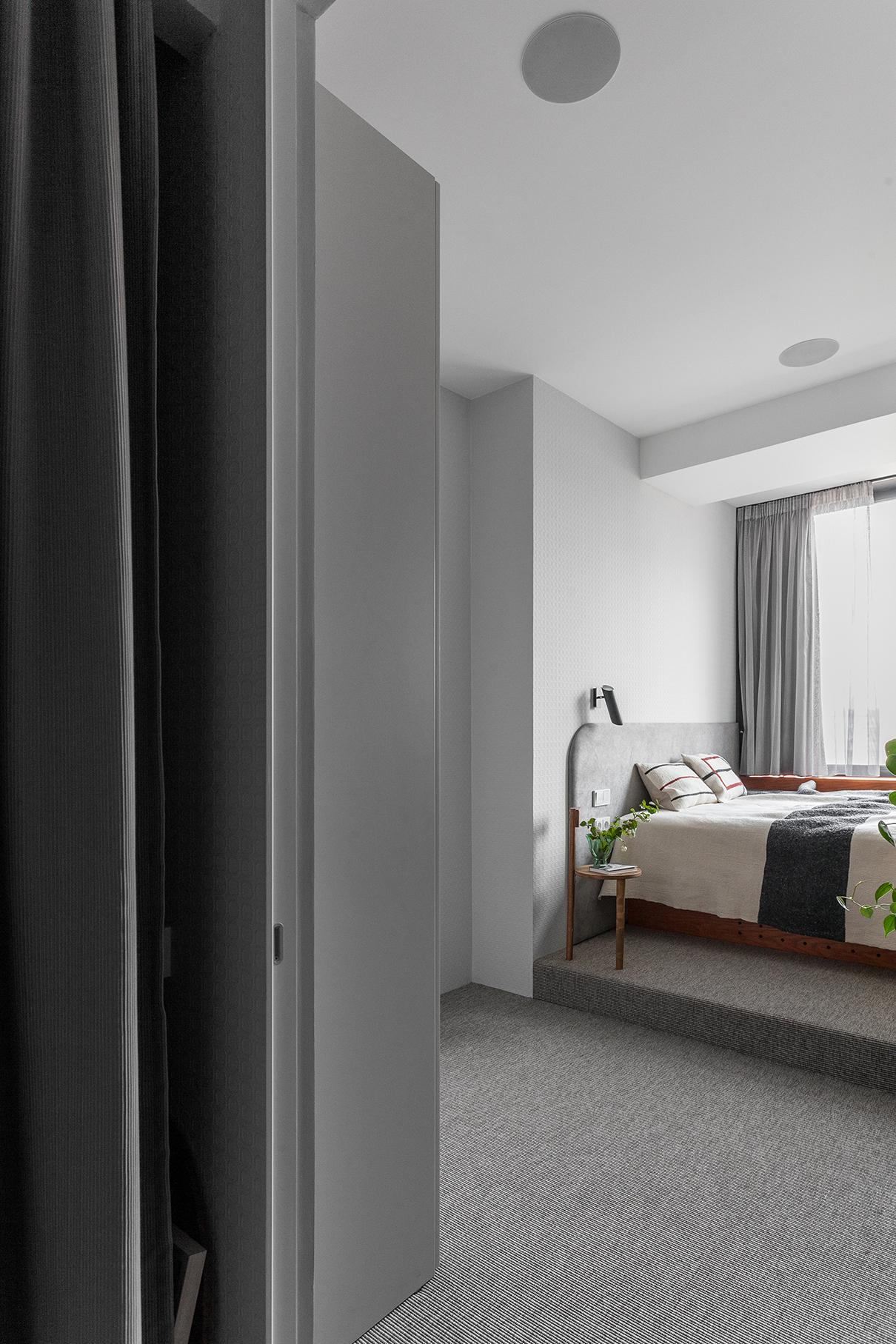 Хозяйскую спальню организовали на месте кухни, официально упразднив газ. Спальное место разместили у окна практически в уровень с подоконником, такую высоту захотели сами заказчики-жаворонки— чтобы с восходом солнца просыпаться бодрыми и полными сил. Для этого конструкцию кровати с мягким изголовьем архитекторы дополнительно поместили на подиум. Задействовали и подоконник, превратив его в прикроватную полку. Пол, переходящий в подиум, укрыт ковровой циновкой Balta Nature. Конструкция кровати разработана студией индивидуально для этого проекта и выполнена из тонированного шпона ясеня