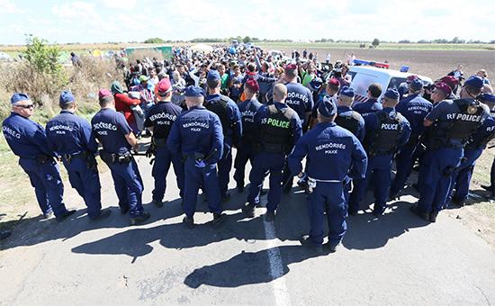 Сотрудники венгерской полиции сдерживают мигрантов у поселка Рёске недалекоотграниц Венгрии иСербии
