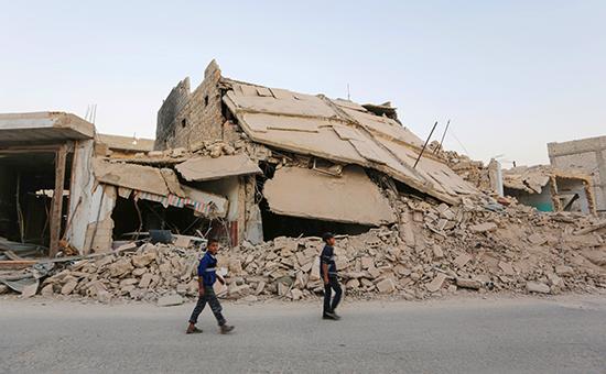 Мальчики проходят миморазрушенных зданий всирийском городе Аль-Раи недалекоотАлеппо, 9 октября 2016 года