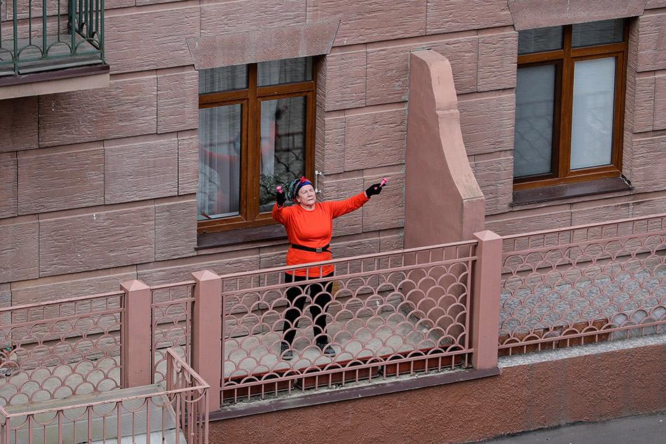 Жительница многоквартирного жилого дома на улице летчика Ивана Федорова в Химках во время зарядки на балконе своей квартиры