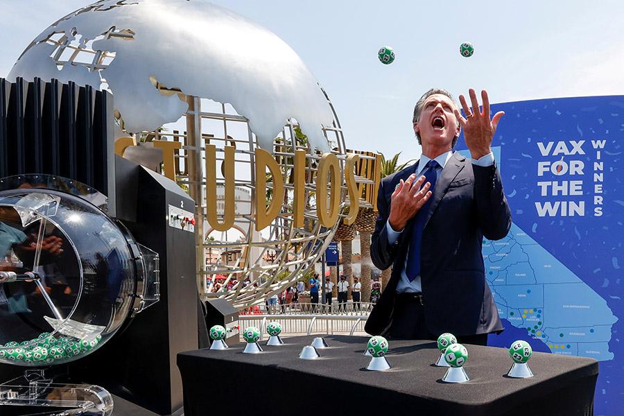 Губернатор Калифорнии Гэвин Ньюсон жонглирует шариком для розыгрыша призов в лотерее Vax for the Win