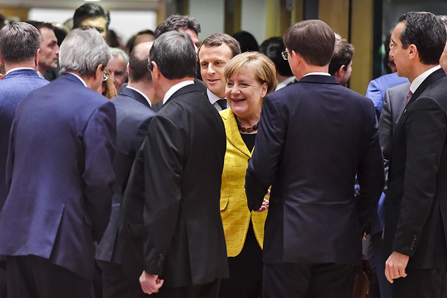 Эмманюэль Макрон и Ангела Меркель (в центре) на встрече лидеров стран Евросоюза на саммите ЕС. 14 декабря 2017 года