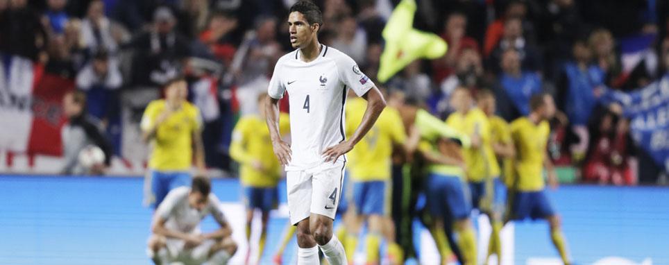 Защитник сборной Франции Рафаэль Варан на фоне празднующих победу шведских футболистов