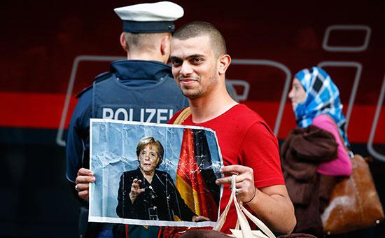 Мигрант держит портрет канцлера Германии Ангелы Меркель после прибытия к главной железнодорожной станции в Мюнхене, Германия