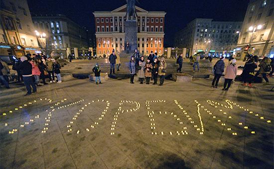 Москвичи у памятника Юрию Долгорукому напротив здания мэрии Москвы во время акции в памятьо погибших в авиакатастрофе Boeing737 в Ростове-на-Дону