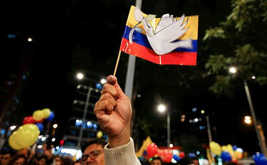 Мужчина сжимает флаг Колумбии. Празднования послезаключения итогового мирного договора междуправительством иповстанцами группировки Революционных вооруженных сил страны (FARC). 25 августа 2016 года