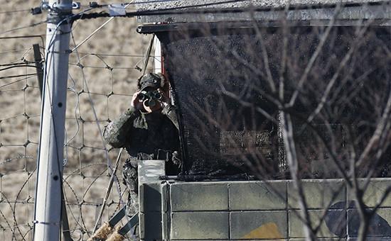 Военнослужащий Южной Кореи смотрит в бинокль через границу
