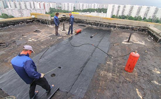 Укладка нового рубероида на крыше во время капитального ремонта многоэтажного панельного дома в Ясенево