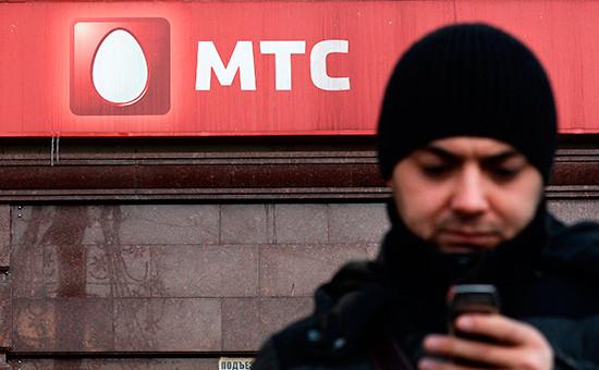 Мужчина стелефоном стоит у офиса компании оператора мобильной связи МТС вМоскве