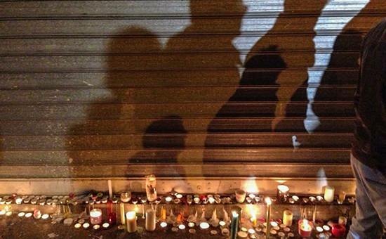 Принесенные парижанами свечи на месте убийства у ресторана Сarillon