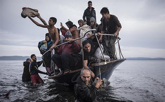 Мигранты прибывают в турецкой лодке на греческий остров Лесбос.Снимок из фотопроекта о беженцах, победившего в номинации «Новостная фотография» Пулицеровской премии