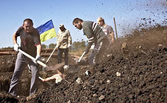 Украинские волонтеры роют ров на границе с Россией. Архивное фото