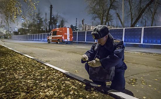 Сотрудник МЧС берет пробу почвы у Московского НПЗ