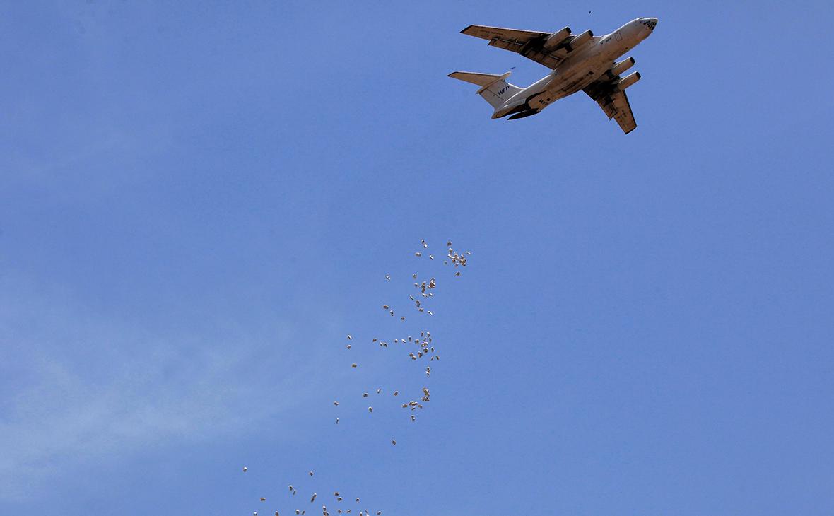 Пакеты с едой сбрасывают с самолета, во время операции по выдаче продовольствия