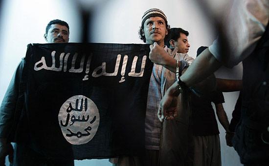 Задержанный в Йемене боевик Аль-Каиды держит флаг с надписью «Нет Бога, кроме Аллаха, и Мухаммед посланник Бога».