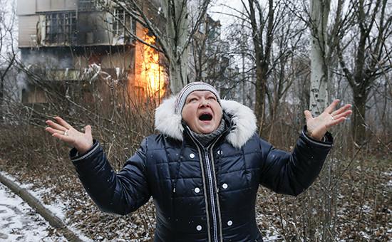 Женщина возле дома, пострадавшего в результате артобстрела Донецка. Архивное фото