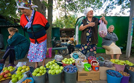 Женщины торгуют овощами и фруктами на рынке города Полтава