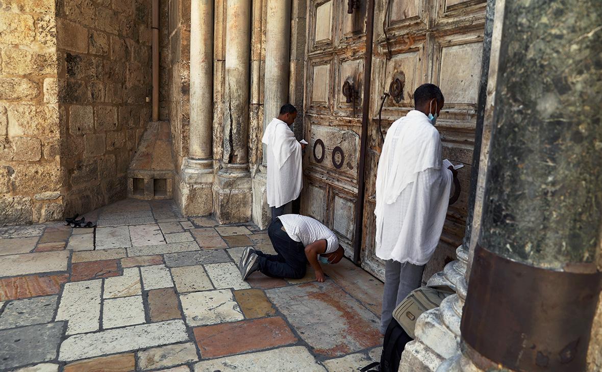 Верующие молятся рядом с закрытыми дверями Храма Гроба Господня в Старом городе Иерусалима, 10 июля 2020г.