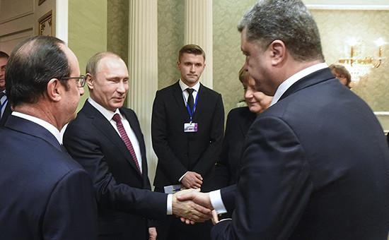 Президент России Владимир Путин и президент Украины Петр Порошенко пожимают друг другу руки во время встречи в Минске, 11 февраля 2015