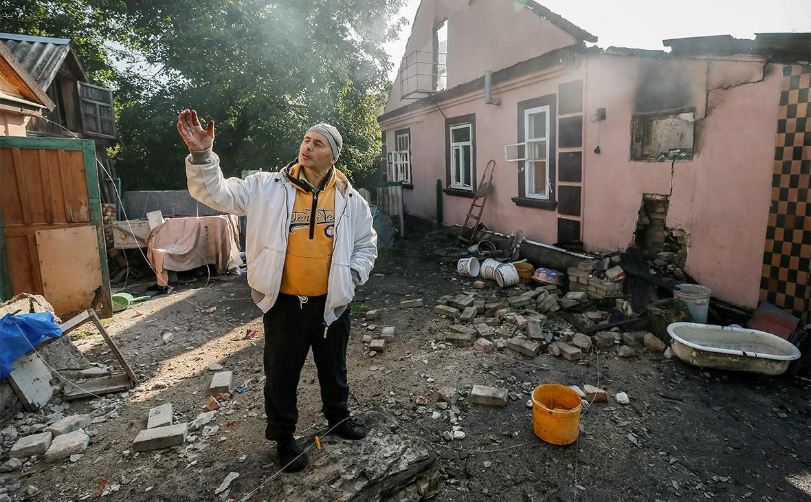 Местный житель у дома, пострадавшего в результате взрыва склада