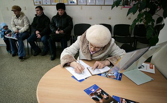Пенсионер заполняет бланки документов в клиентской службе отделения Пенсионного фонда РФ