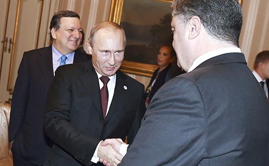 Президент России Владимир Путин (в центре) пожимает руку президенту Украины Петру Порошенко на саммите в Милане