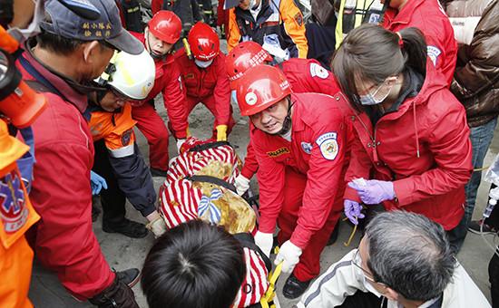 Тайвань.Спасатели извлекают жертву землетрясения из под обломков разрушенного здания в Тайнане