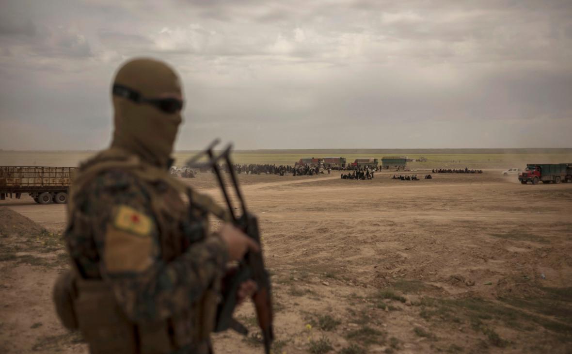 Член SDF на фоне колонны людей, эвакуирующихся из Багуза