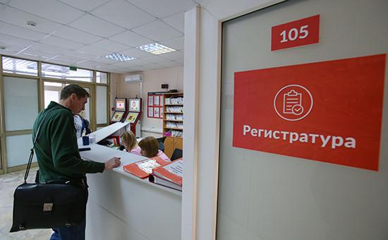 Посетитель у регистрационного стола вполиклинике