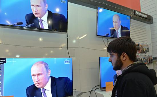 Житель Грозного смотрит пресс-конференцию президента РФ Владимира Путина в торговом центре города