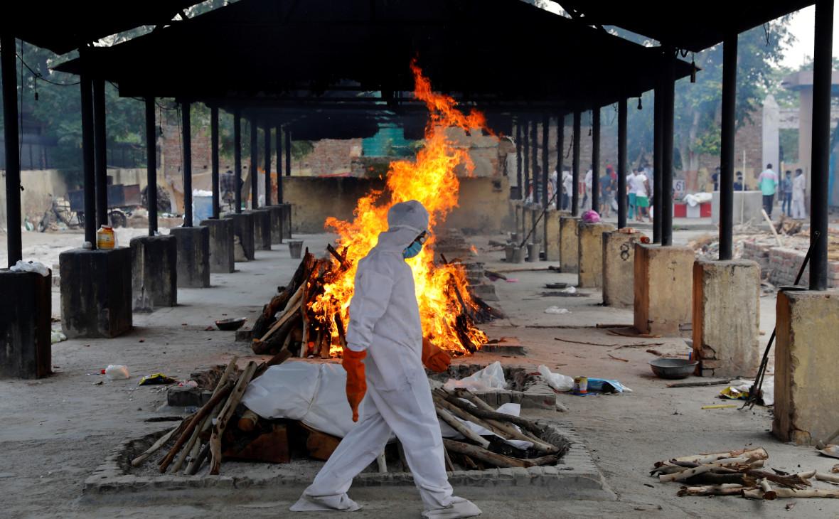 Священник, одетый в защитный костюм, проходит рядом с погребальным костром, приготовленным для сжигания тела умершего от COVID-19. Нью-Дели, Индия