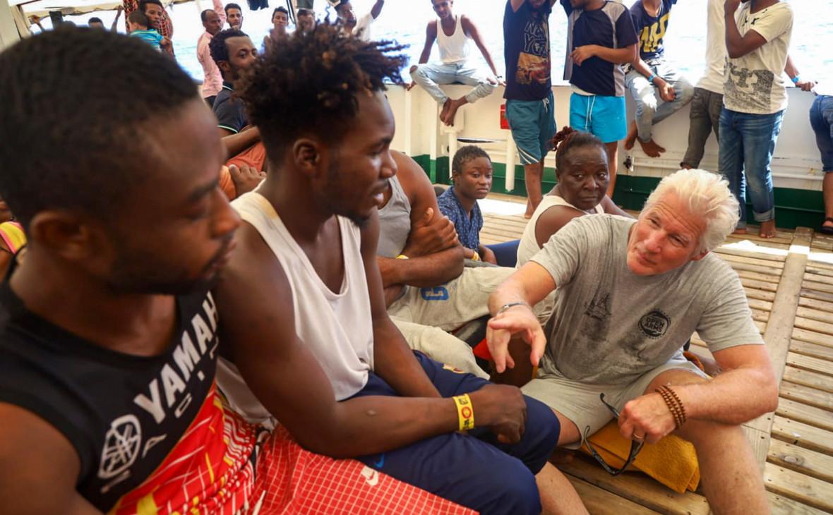 Ричард Гир (справа) на судне с мигрантами