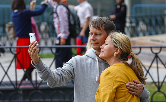 Люди фотографируются на телефон
