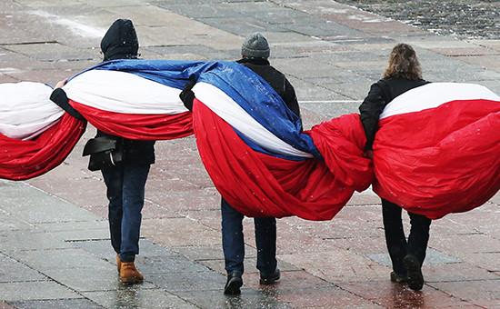 Люди несут флаг России
