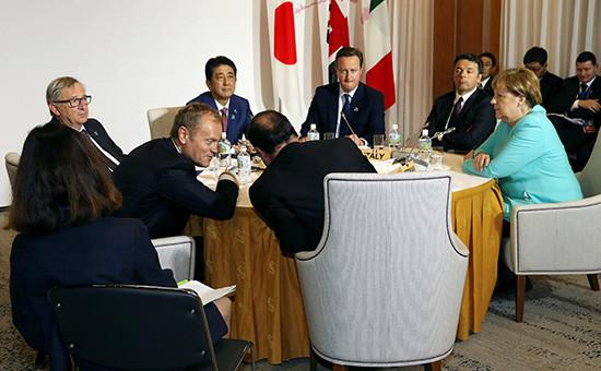 За столом (слева направо):председатель Европейского совета Дональд Туск, премьер-министр Японии Синдзо Абэ, президент Франции Франсуа Олланд, премьер-министр Великобритании Дэвид Кэмерон, премьер-министр Италии МаттеоРенци и канцлер Германии Ангела Меркель во время саммита G7. Япония,26 мая, 2016 года