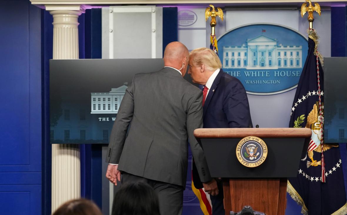 Охрана уводит Дональда Трампа (справа) с пресс-конференции