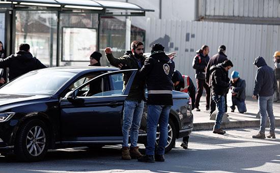 Сотрудники турецкой полиции досматривают прохожих недалеко от места теракта