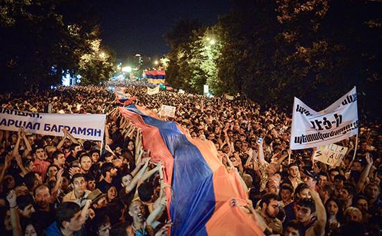 Протестующие несут огромный национальный флаг во время акции протеста против повышения цен на электроэнергию в Ереване