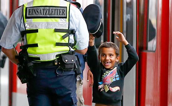 Маленький мигрант примеряет фуражку сотрудника полиции на вокзале в Мюнхене