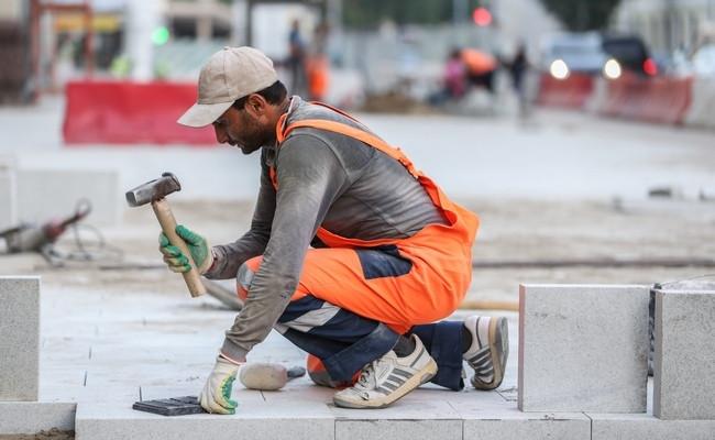 Рабочий вовремя укладки плитки наТверском бульваре вМоскве