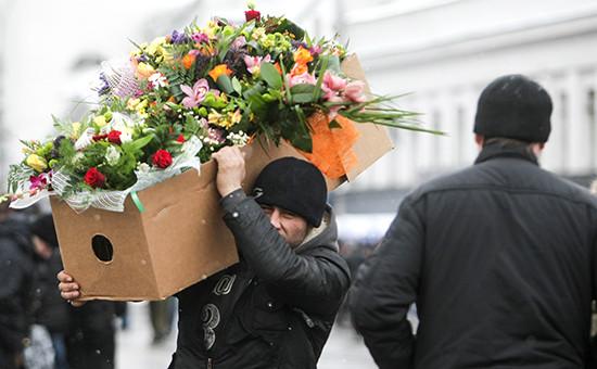 Продавец несет коробку сбукетами цветов вМоскве