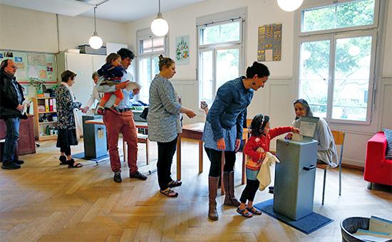 Жители Берна голосуют научастке, расположенном вшколе