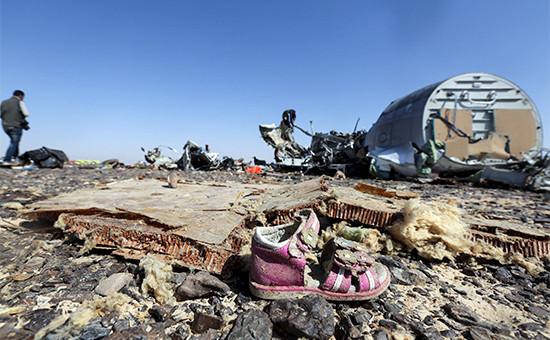 Детский ботиночек на фоне обломков лайнера А321 компании «Когалымавиа», разбившегося в Египте