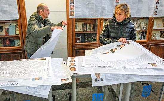 Работники избирательной комиссии готовят плакаты с информацией о политических партиях на избирательном участке в Киеве. 25 октября 2014 года