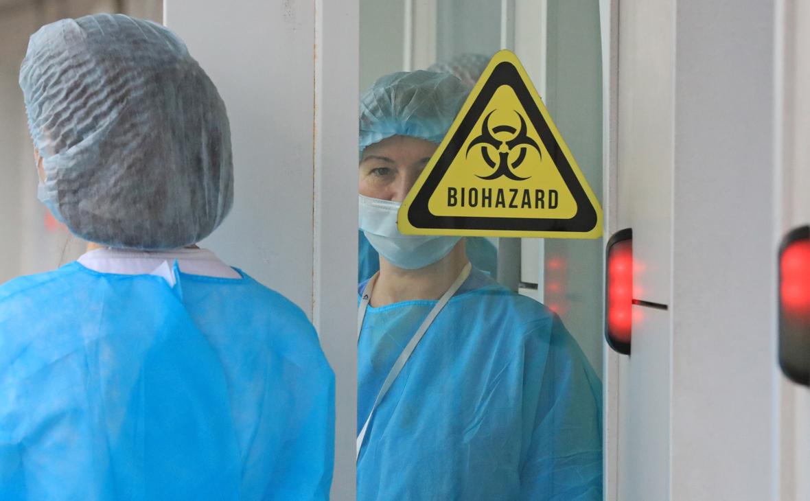 Медицинские сотрудницы у двери со знаком, предупреждающим о биологической опасности, в здании ГБУЗ «Клиническая инфекционная больница им. С.П.Боткина»