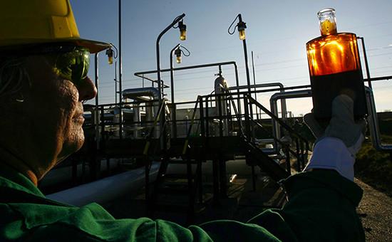 Рабочий изучает образец нефти