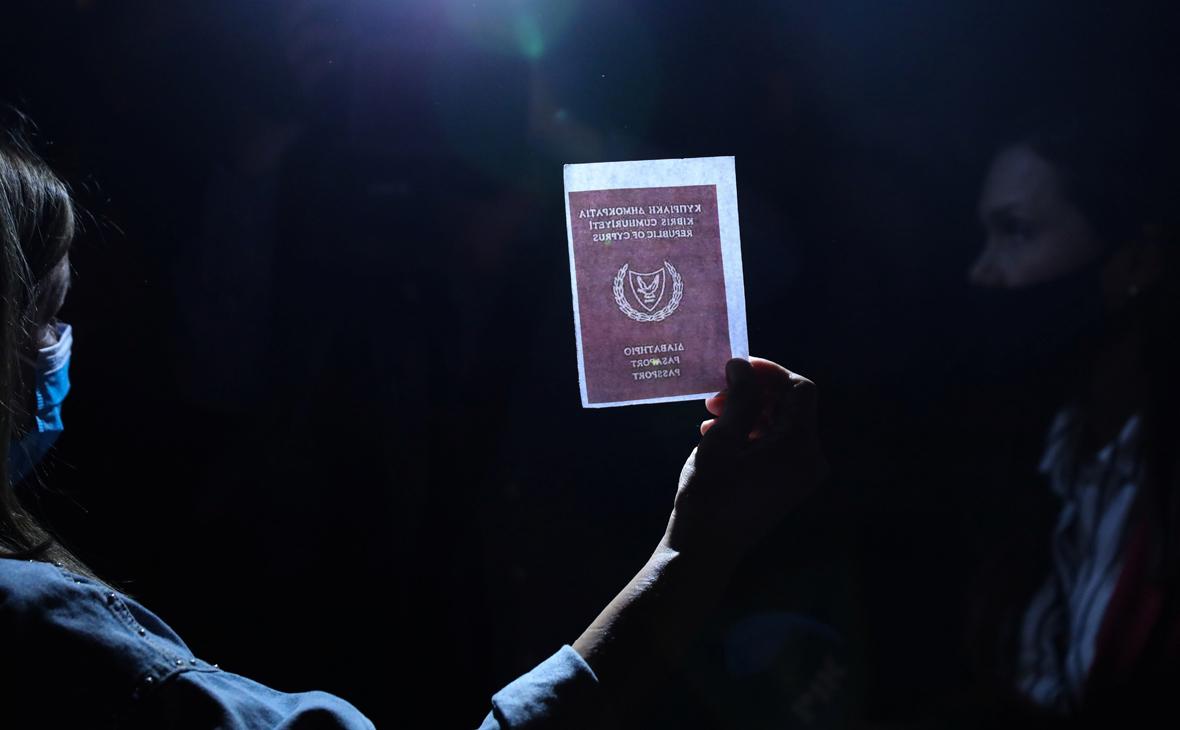 Человек держит изображение паспорта во время акции протеста против коррупции