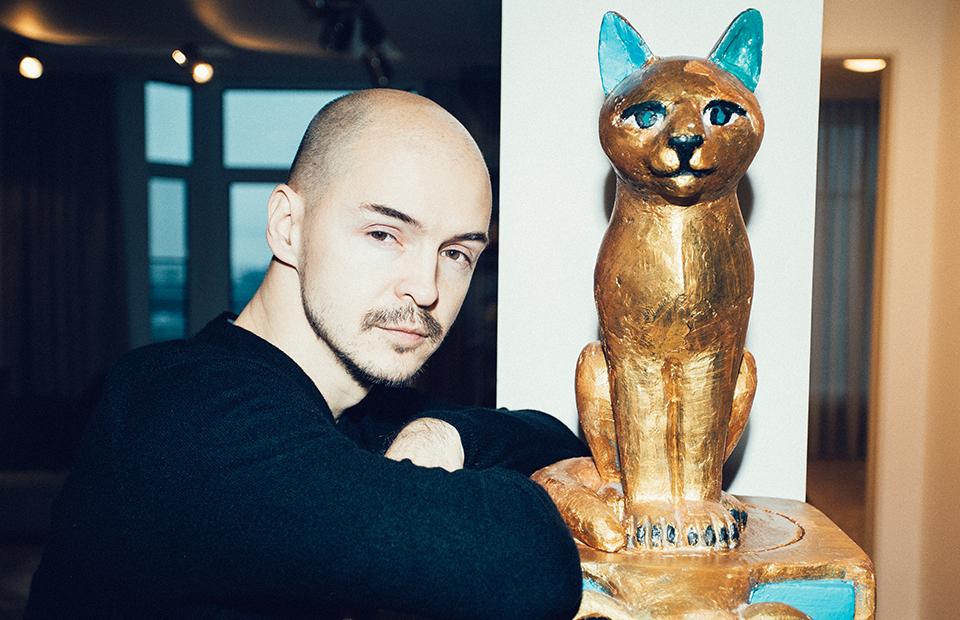 Дмитрий Волков у скульптуры «Триумф кота» работы Александра Повзнера